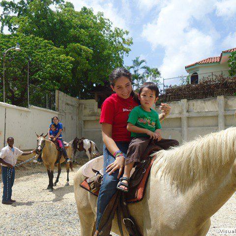 un niño y una joven montados en un caballo